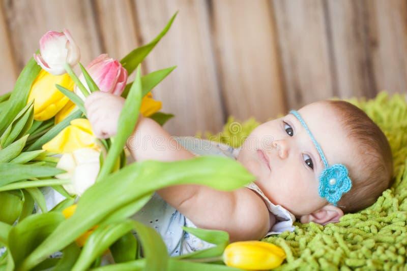 有郁金香的可爱的女婴 免版税库存照片