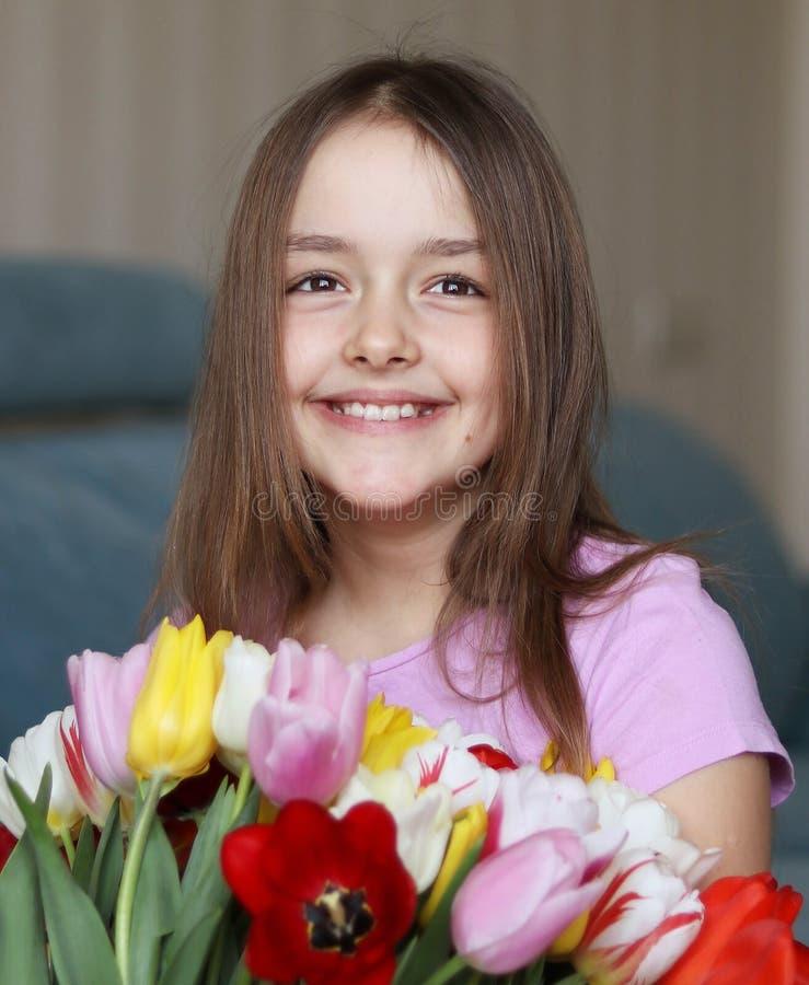有郁金香的可爱的微笑的小女孩,关闭,室内 免版税库存照片