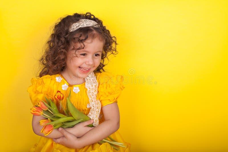 有郁金香的女孩在黄色背景的手上 免版税图库摄影