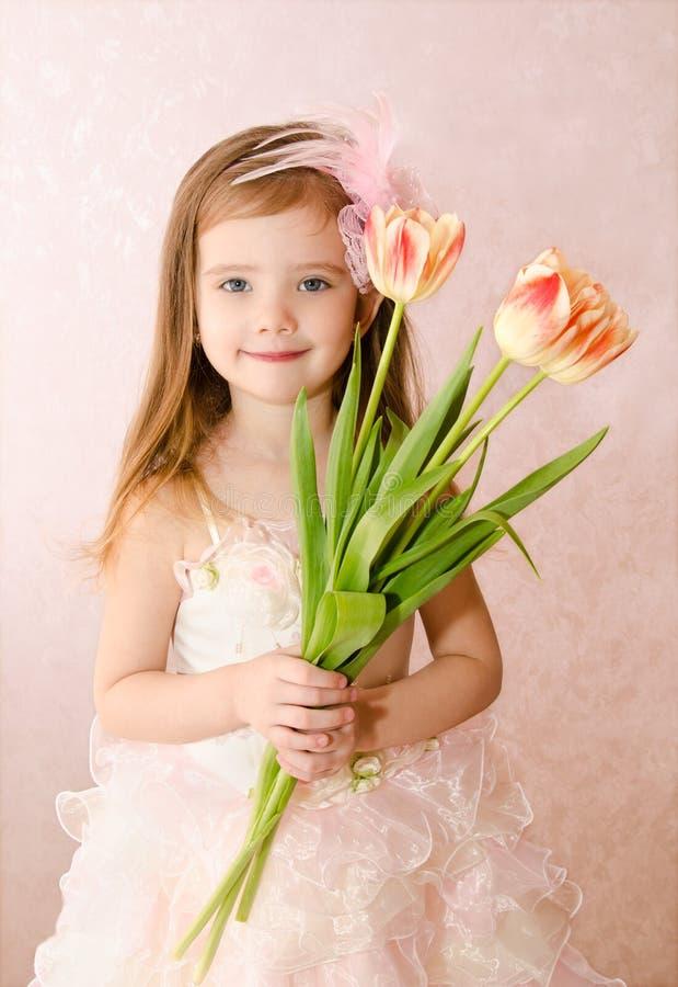 有郁金香的微笑的小女孩 图库摄影