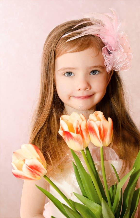 有郁金香的微笑的小女孩 库存图片