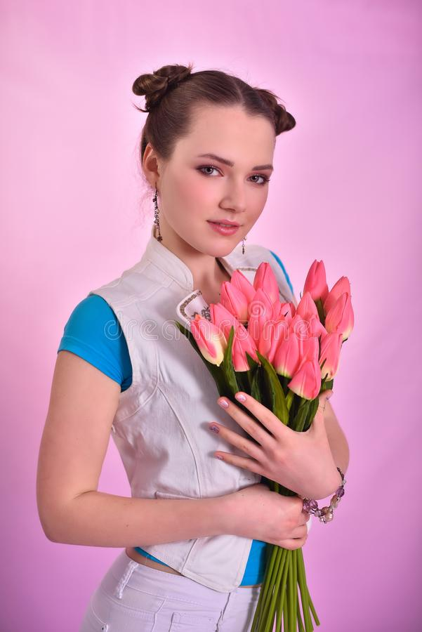 有郁金香花束的女孩在桃红色背景的 免版税库存照片