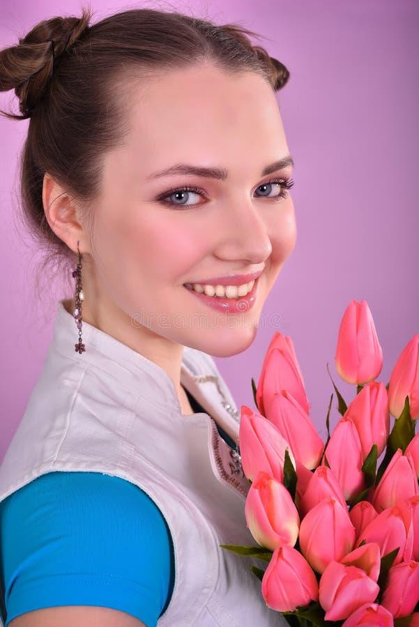 有郁金香花束的女孩在桃红色背景的 免版税库存图片
