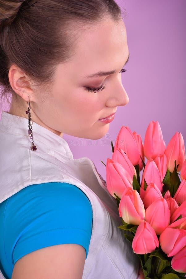 有郁金香花束的女孩在桃红色背景的 库存照片