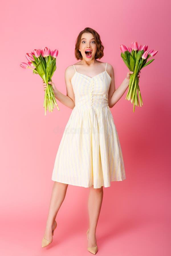 有郁金香花束的激动的妇女  免版税库存图片