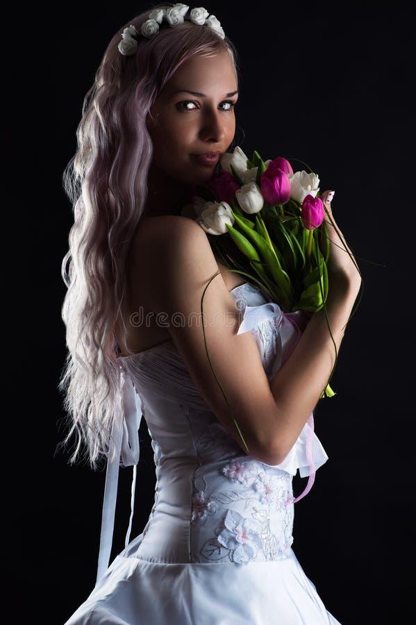 有郁金香花束的迷人的妇女  免版税库存照片
