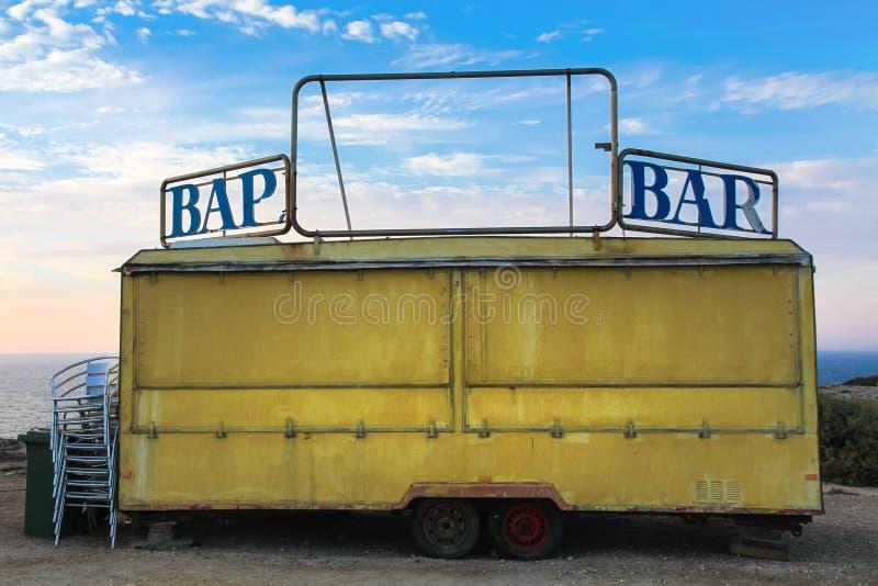 有部分地打破的词酒吧的老黄色酒吧拖车车 库存照片