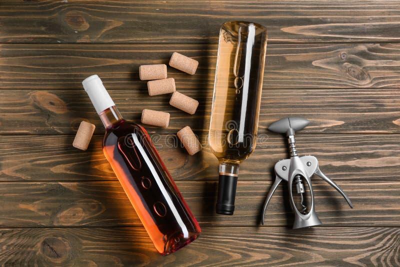 有酒和拔塞螺旋不同形式的瓶在木背景 免版税图库摄影