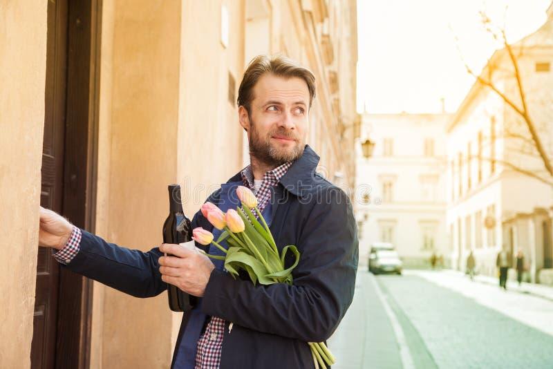有酒和花花束敲响的门铃的人 免版税库存照片