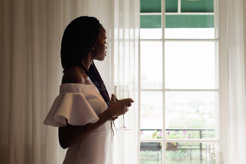 有酒杯的典雅的可爱的非洲夫人通过窗口看 她穿白色礼服 免版税库存照片