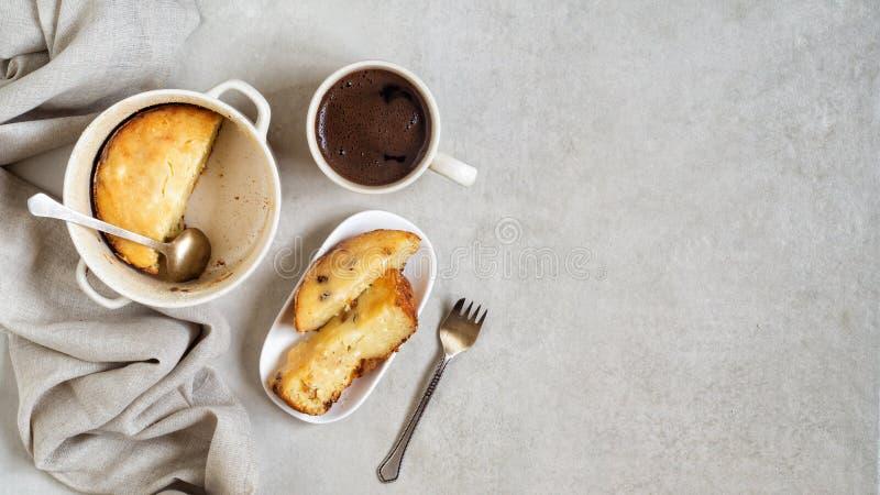 有酸奶干酪砂锅的平底锅,切片在板材的砂锅和咖啡在灰色桌上的 免版税库存图片
