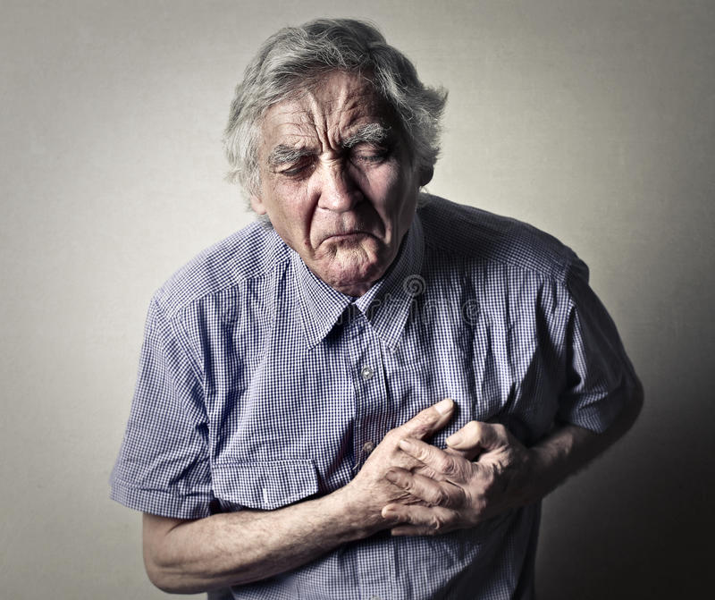 有酸疼的胸口的老人 免版税库存图片
