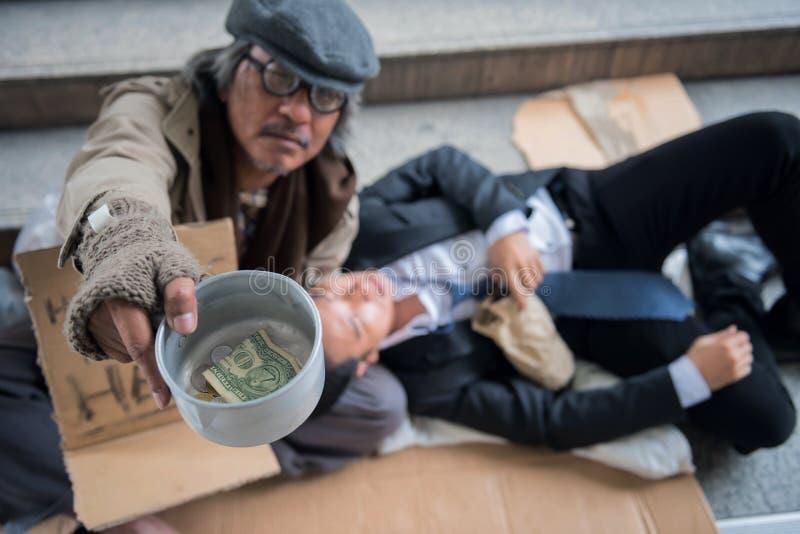 有醉酒的商人的叫化子在城市 库存图片