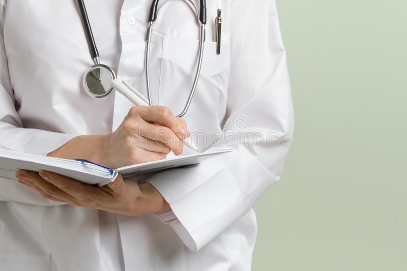 有采取关于她的笔记薄的听诊器的医生妇女笔记反对绿色背景 复制空间 免版税库存图片