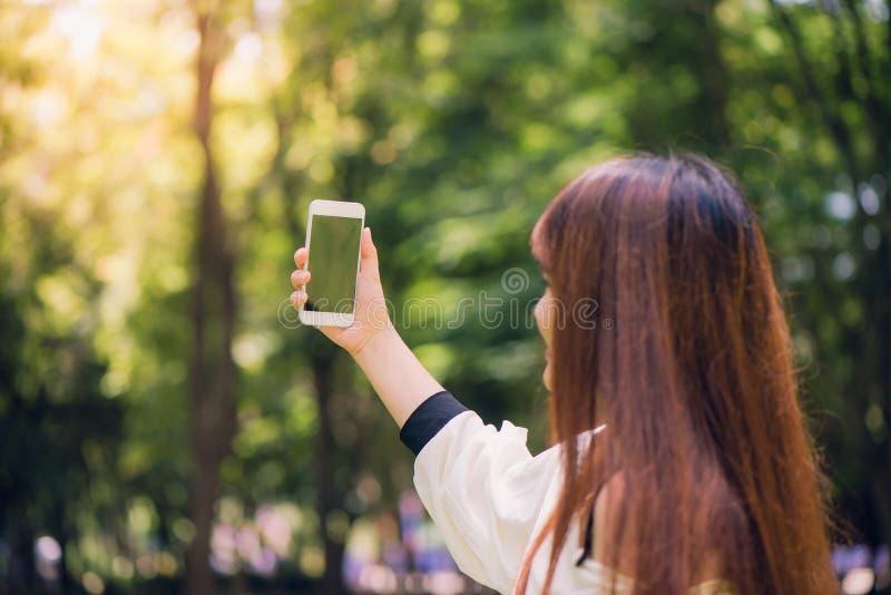 有采取在她的电话的长的棕色头发的年轻美丽的亚裔妇女一selfie在公园 自然照明设备 免版税库存图片