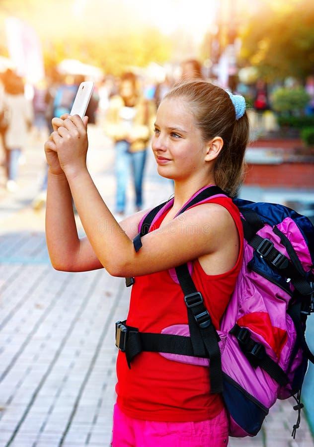 有采取在智能手机的背包的旅游女孩selfies 免版税库存图片