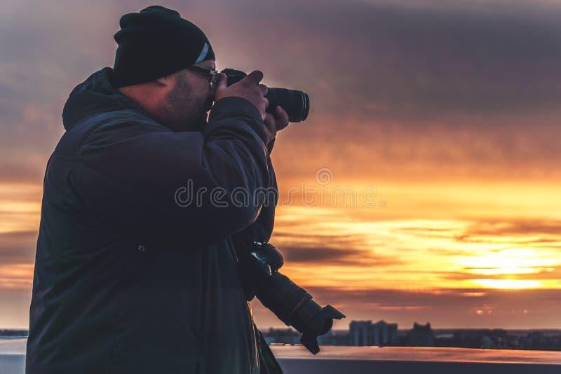 有采取日落的射击从屋顶的两台照相机的摄影师 免版税库存图片