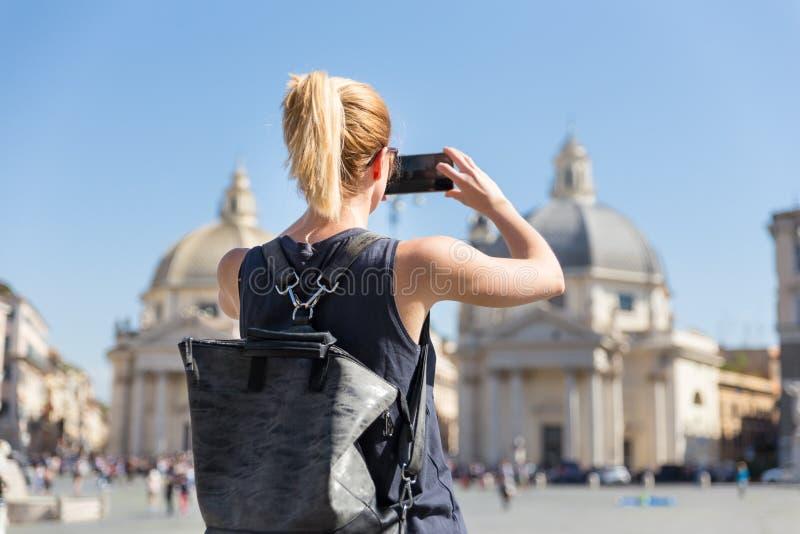 有采取照片oof Piazza del Popolo的一个fashinable葡萄酒行家背包的女性游人在罗马,由她的意大利 免版税图库摄影