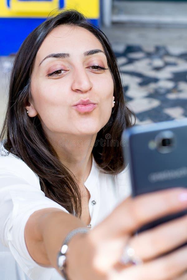 有采取selfie和做一张滑稽的面孔的黑发和白色衬衣的女孩 免版税库存图片