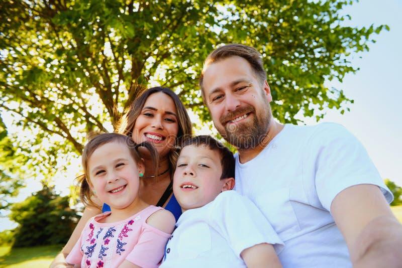 有采取selfie的孩子的愉快的家庭在公园 免版税图库摄影