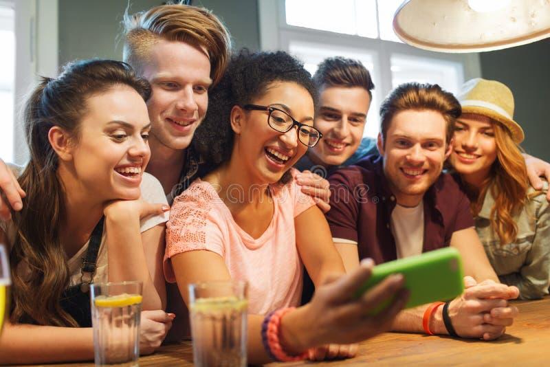 有采取selfie的智能手机的愉快的朋友在酒吧 免版税库存图片