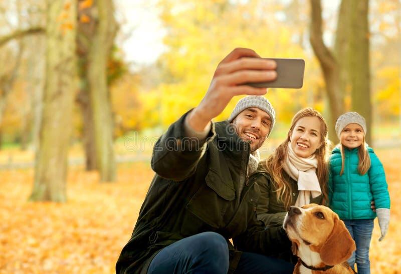 有采取selfie的狗的幸福家庭在秋天公园 免版税库存照片