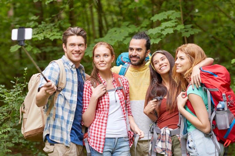 有采取selfie的背包的朋友由智能手机 库存图片