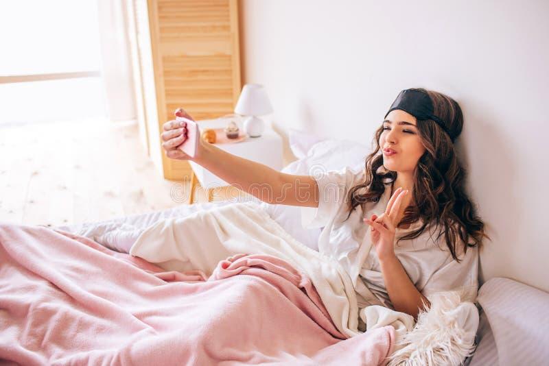 有采取selfie nd的黑发的年轻女人摆在电话照相机 单独在卧室 在睡衣的美好的模型 ?? 免版税库存照片