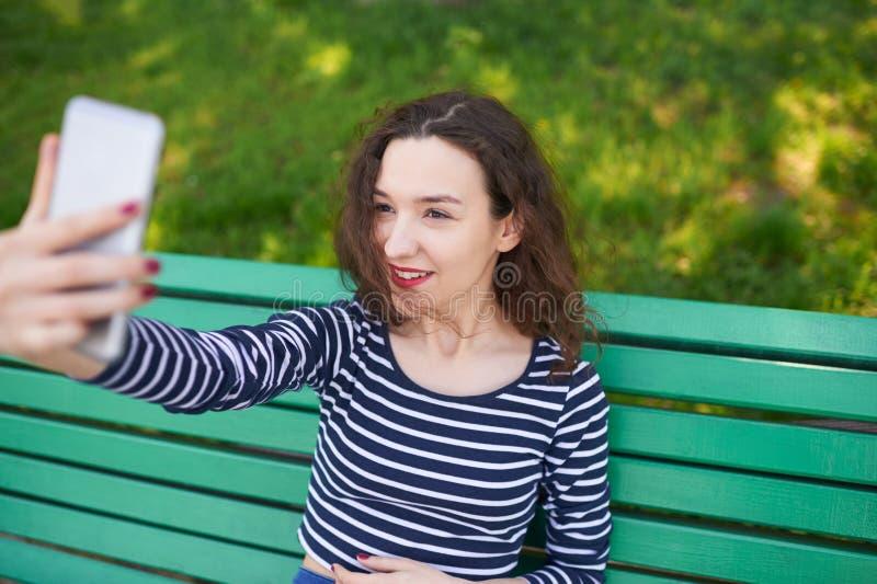 有采取selfies的卷曲发型的美丽的女孩 免版税库存照片