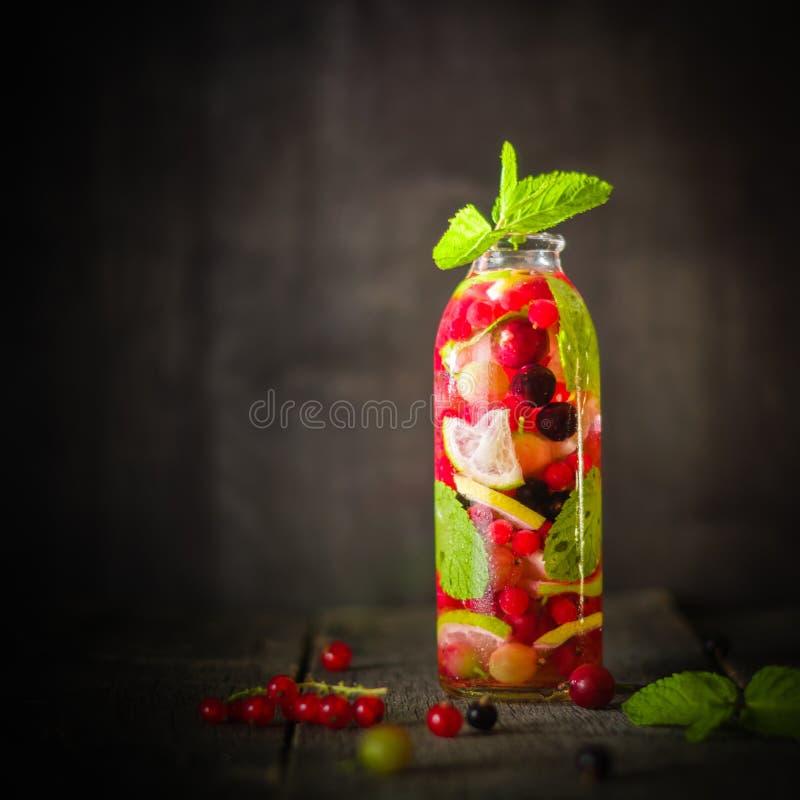 有里面戒毒所水、莓果和柑橘的瓶 黑暗的背景和老木桌表面 免版税库存图片