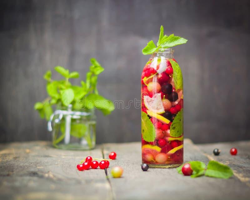 有里面戒毒所水、莓果和柑橘的瓶 黑暗的背景和老木桌表面 免版税图库摄影