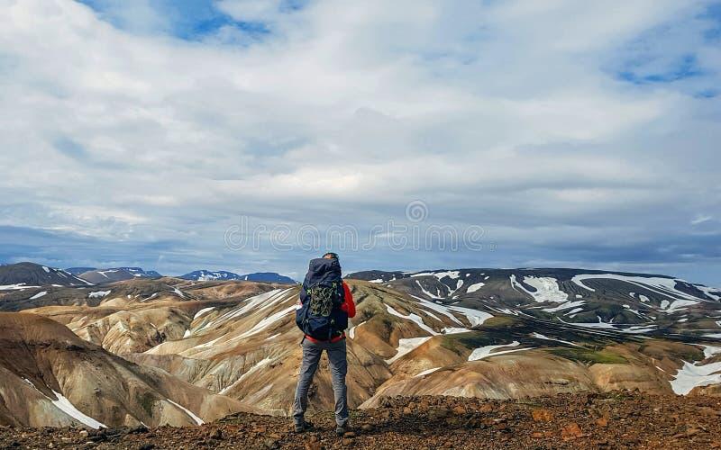 有重的巨大的背包身分的老练的徒步旅行者妇女和看流纹岩山兰德曼纳劳卡冰岛 免版税库存照片