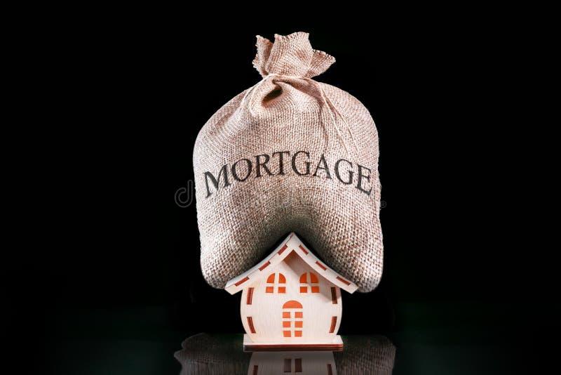 有重的房屋贷款 与金钱的袋子抵押的 在房子的抵押压力 免版税图库摄影