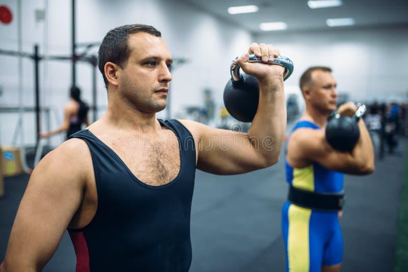 有重量的在健身房,kettlebell举运动员 免版税图库摄影