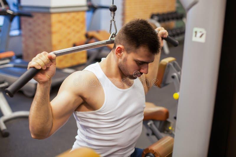 有重量训练的人在健身房设备体育俱乐部 免版税库存照片