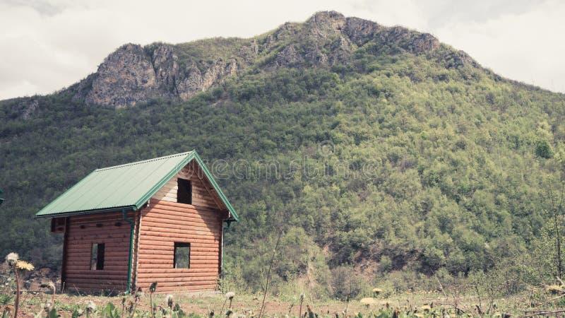 有野花和一间老木农舍的一个高山草甸 小屋客舱在农村秋天风景的山阿尔卑斯 免版税库存照片