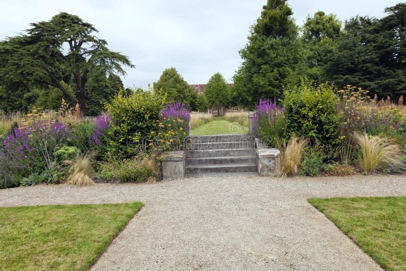 有野花植物、石台阶和石渣道路的庭院 图库摄影