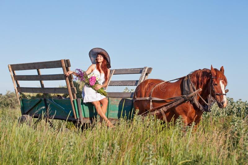 有野花的俏丽的女孩在马支架在夏日 免版税库存图片