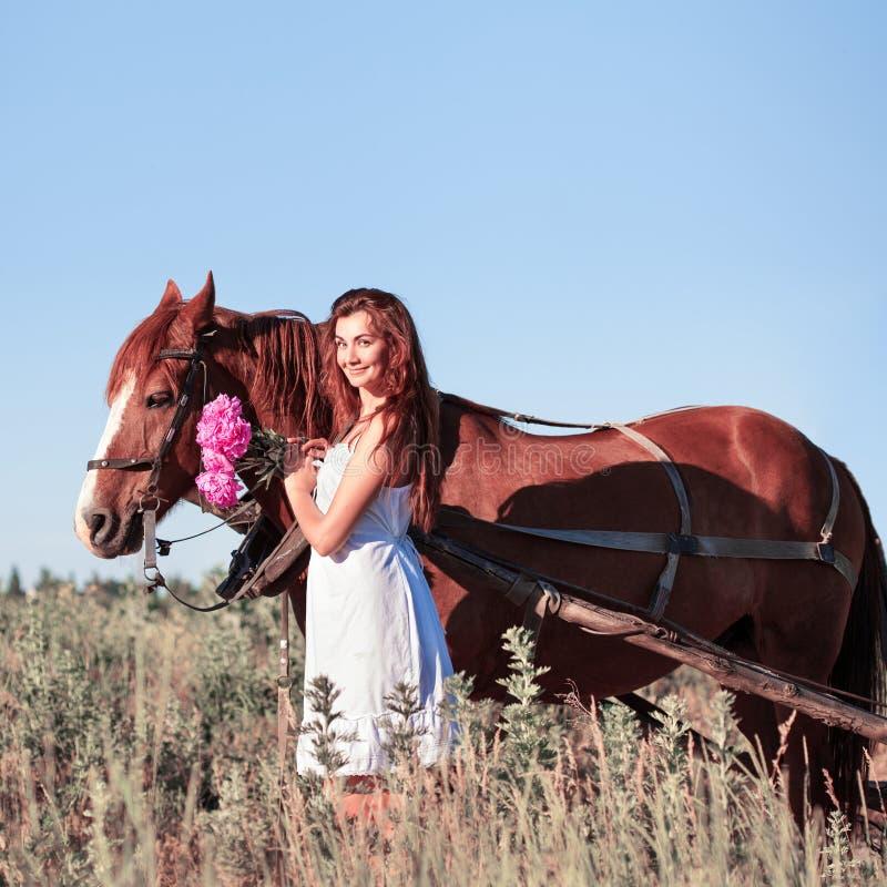 有野花的俏丽的女孩在马支架在夏日 库存照片