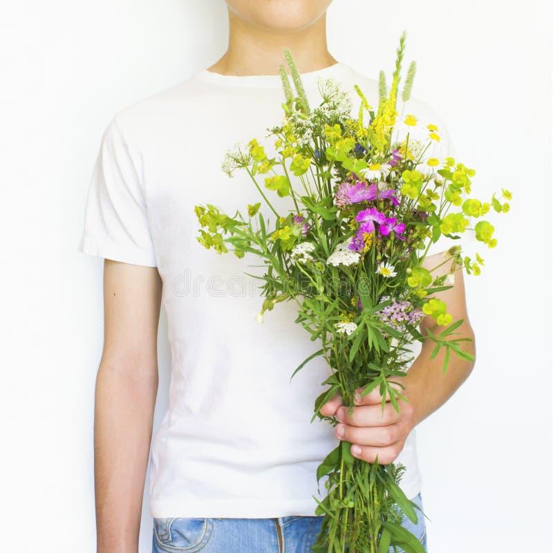 有野花的年轻人 免版税库存照片