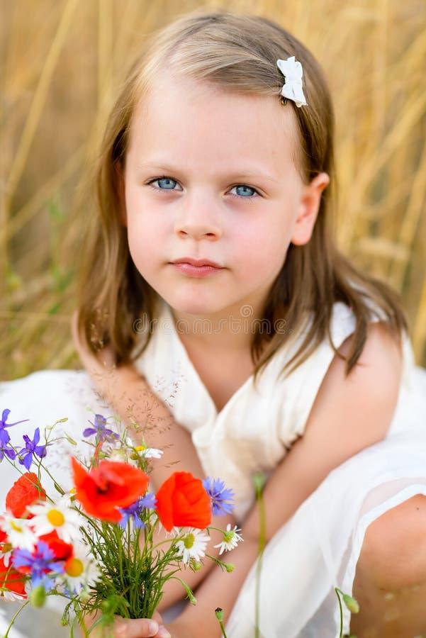 有野花红色鸦片花束的逗人喜爱的小女孩 免版税库存图片