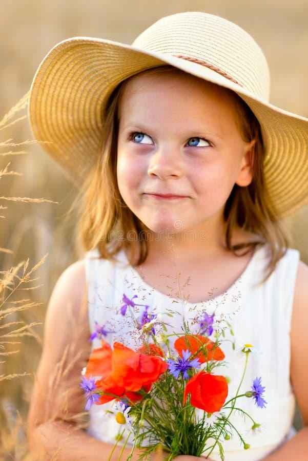 有野花红色鸦片花束的逗人喜爱的小女孩 库存图片