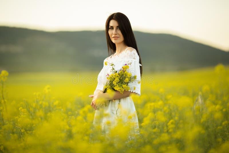 有野花花束的俏丽的妇女在黄色领域的在日落点燃,夏时 图库摄影