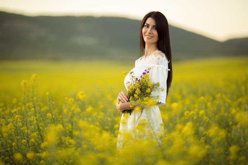 有野花花束的俏丽的妇女在黄色领域的在日落点燃,夏时 免版税库存照片