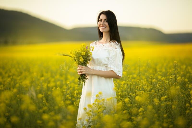 有野花花束的俏丽的妇女在黄色领域的在日落点燃,夏时 免版税库存图片