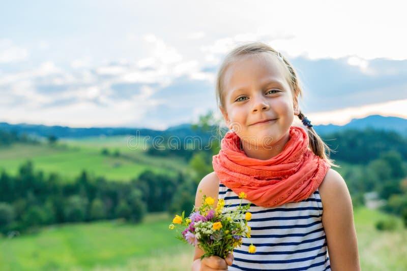 有野花花束的小女孩在a背景的  免版税库存照片