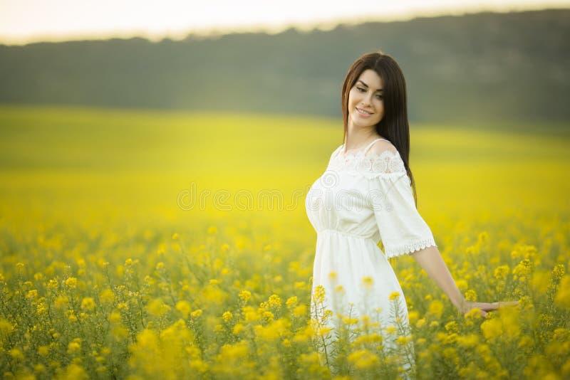 有野花花束的愉快的少妇在黄色领域的在日落点燃,夏时 免版税图库摄影