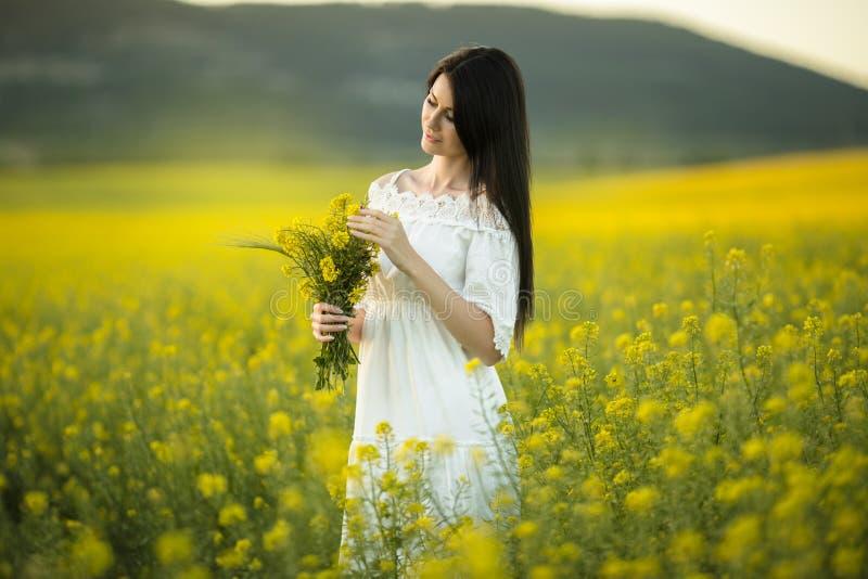 有野花花束的愉快的少妇在黄色领域的在日落点燃,夏时 免版税库存图片