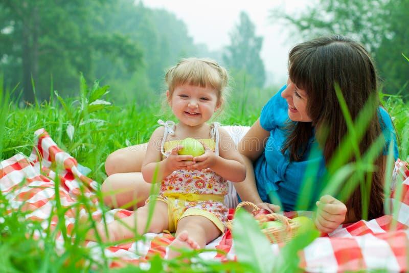 有野餐吃苹果的母亲和女儿 库存图片