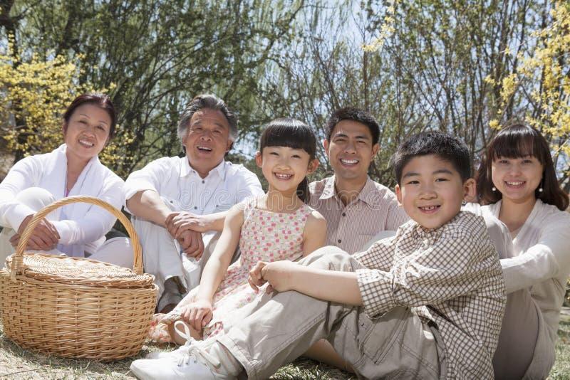 有野餐和享用公园的一个多代家庭的画象在春天 库存照片